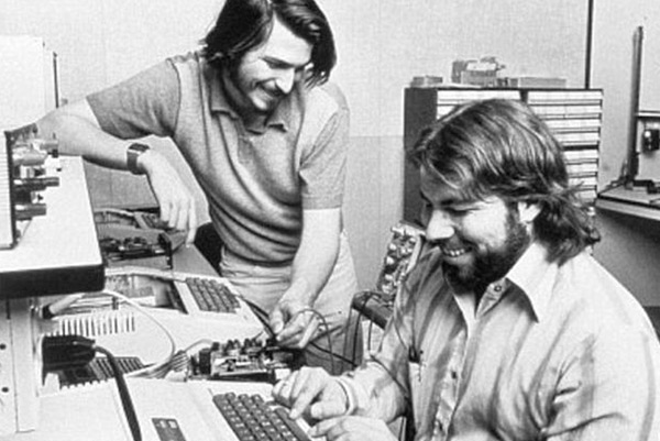 Steve Jobs and Wozniak working on computers in the garage.