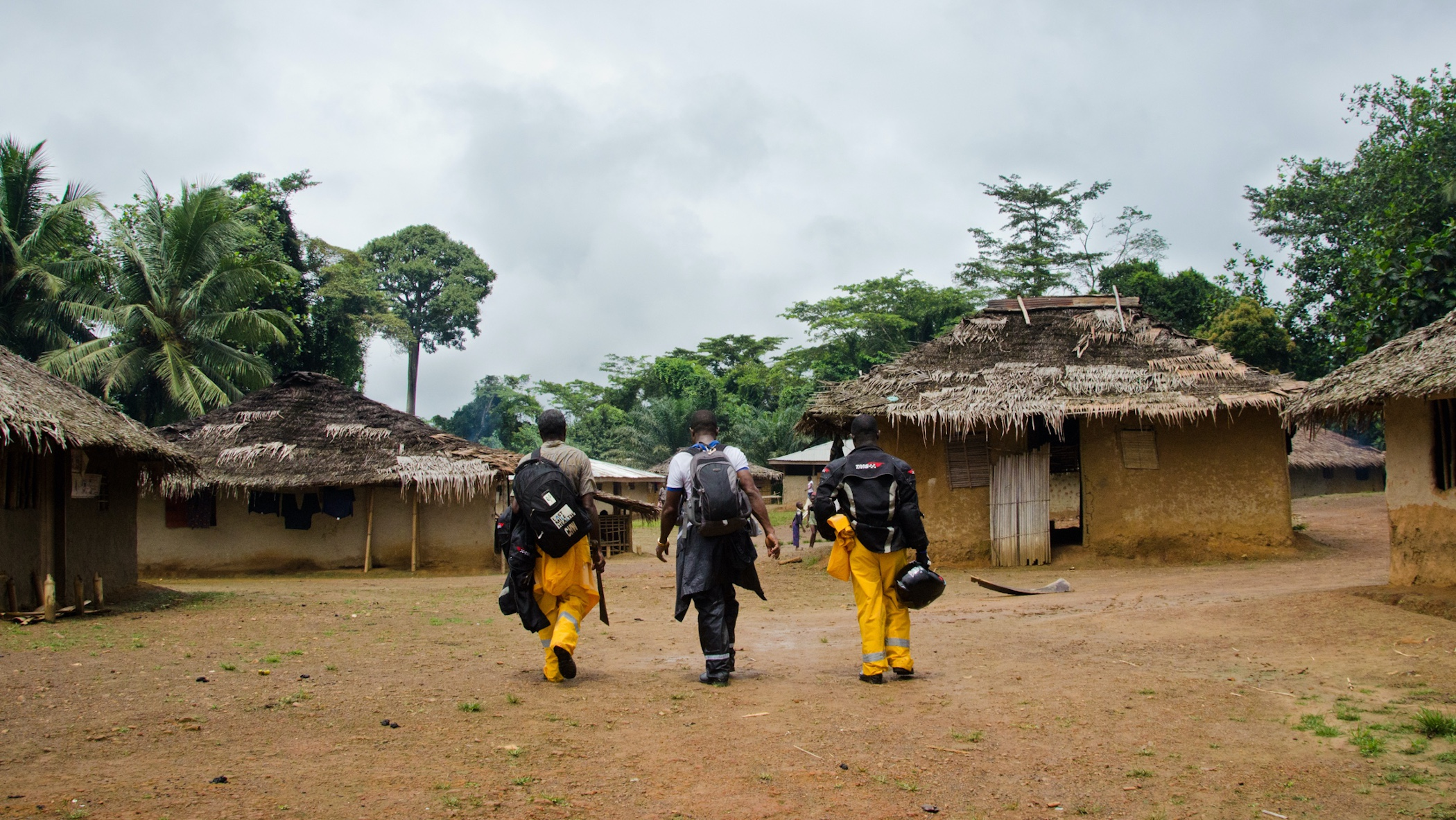 Three people walking with their backs to the camera.